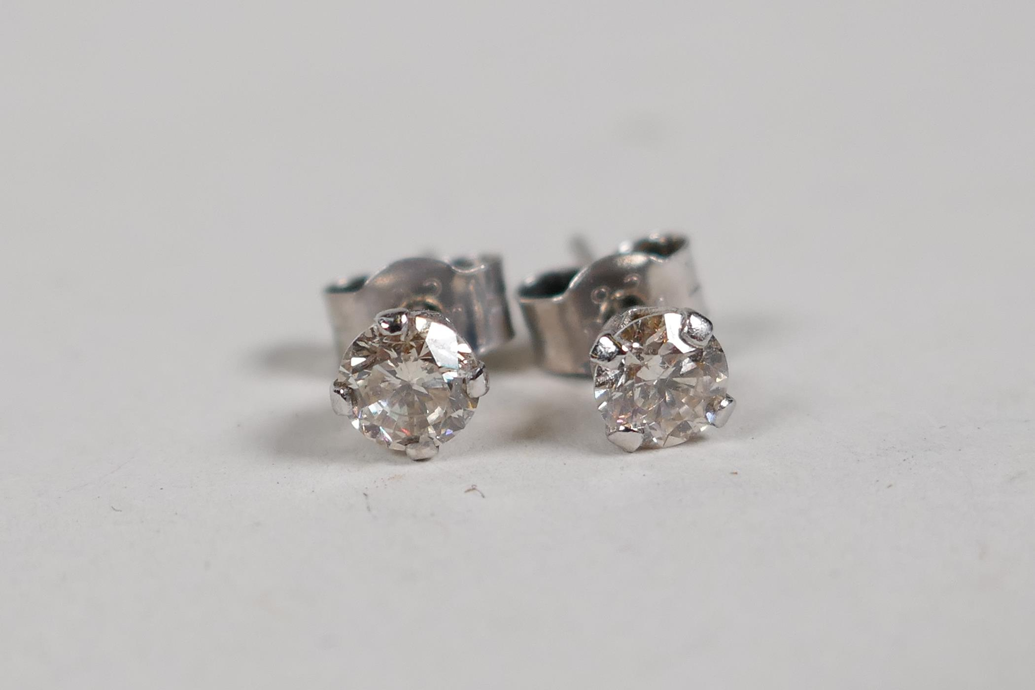A pair of 14ct white gold diamond stud earrings, approx 0.5ct