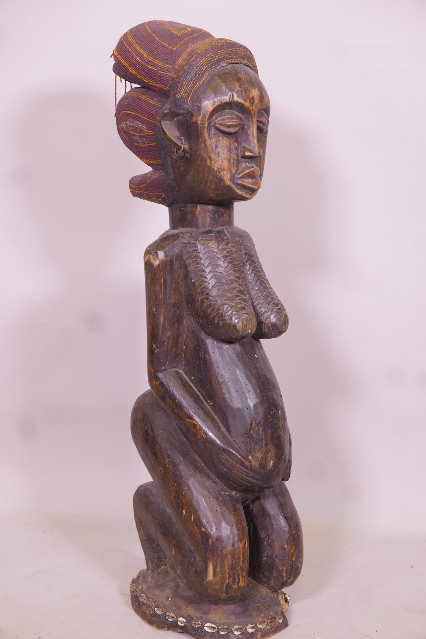 An antique African carved wood fertility figure with beaded headdress and inset with sea shells, - Image 4 of 5