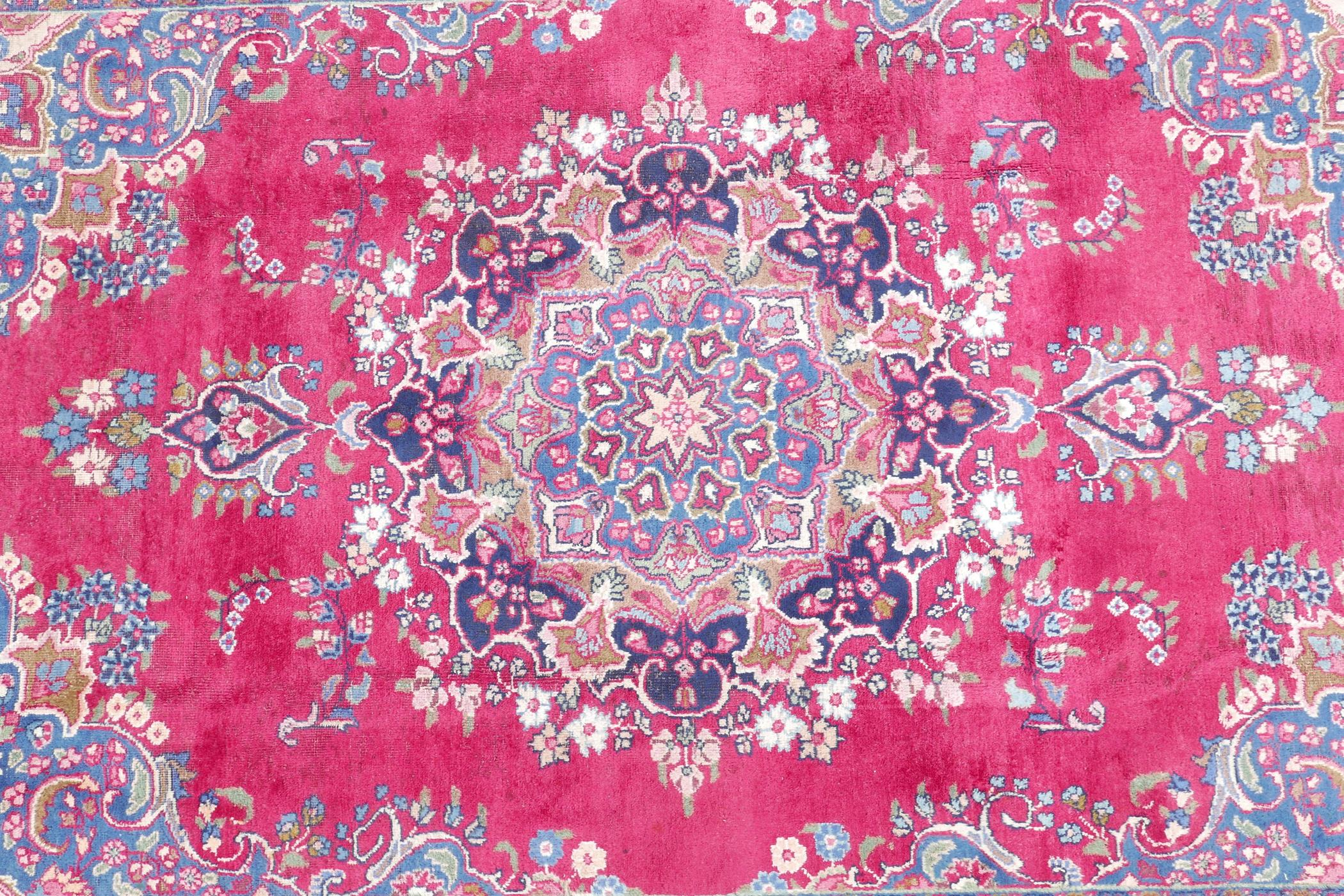 """A pink/red ground Persian Kashmar carpet with a floral medallion design, 77"""" x 117"""""""