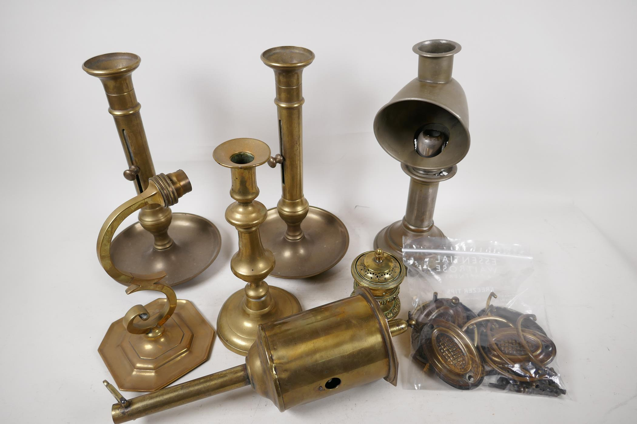 A quantity of brassware including a C19th meat jack, ejector candlesticks, drawer handles etc