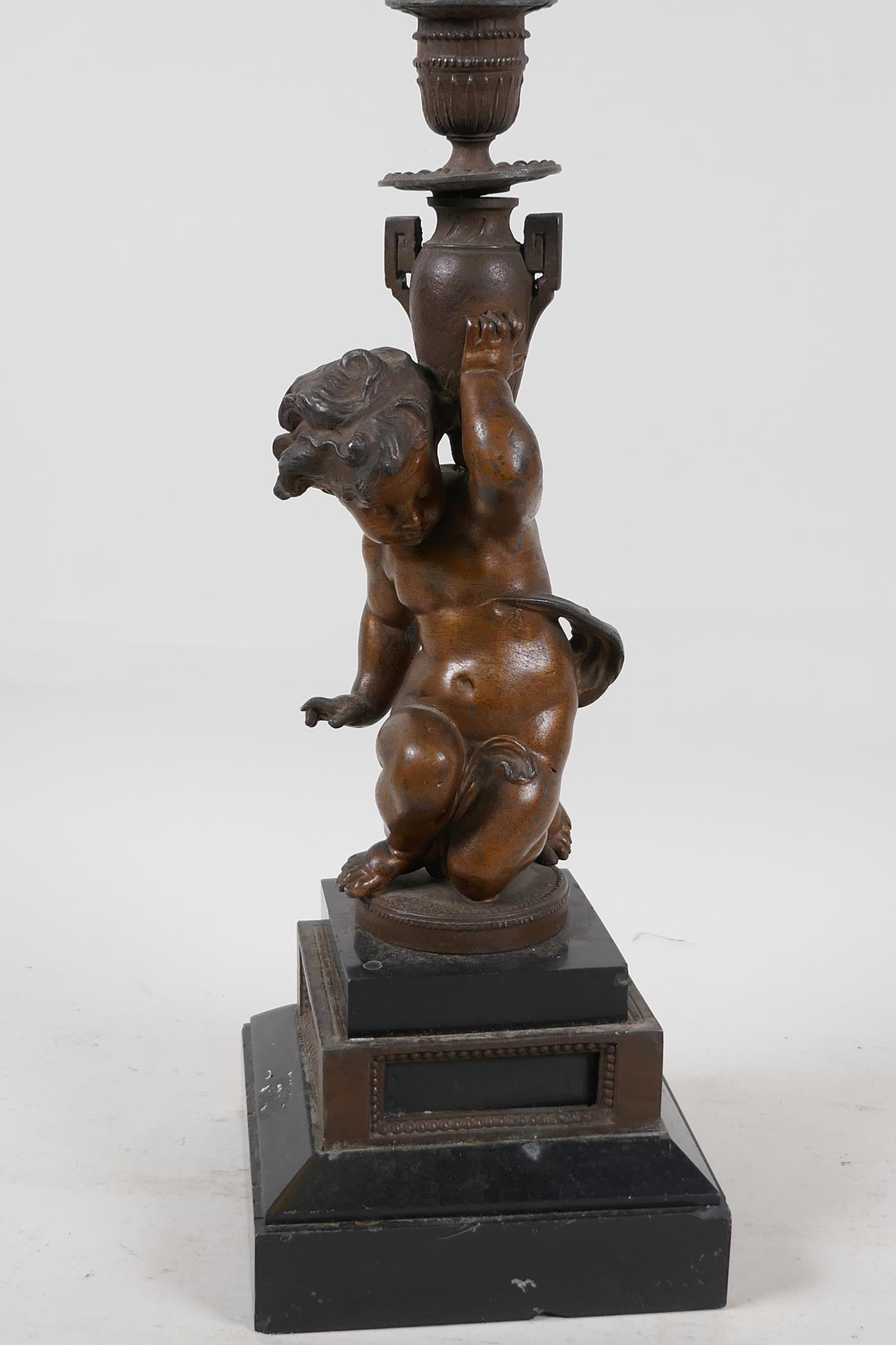 """A C19th bronze candlestick cast as a cherub, raised on stepped marble base, 13"""" high"""