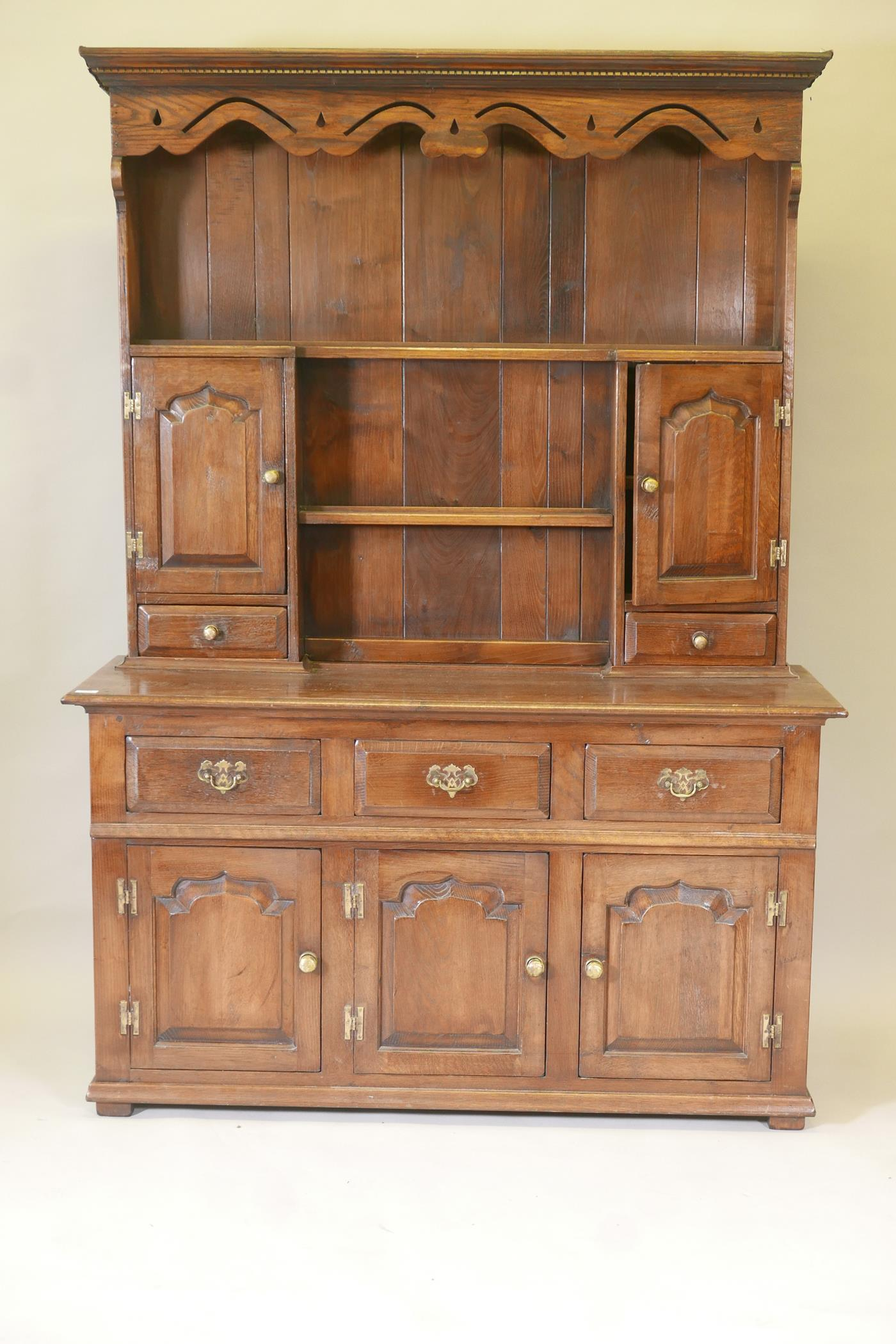 An oak dresser and plate rack with three drawers over three doors to the base, the upper section