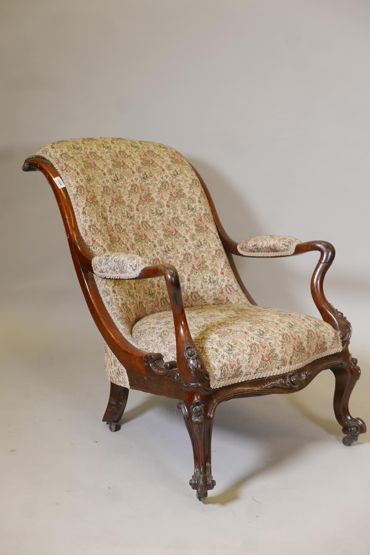 A Victorian rosewood show frame open arm easy chair, with scrolled back and shaped arms, raised on