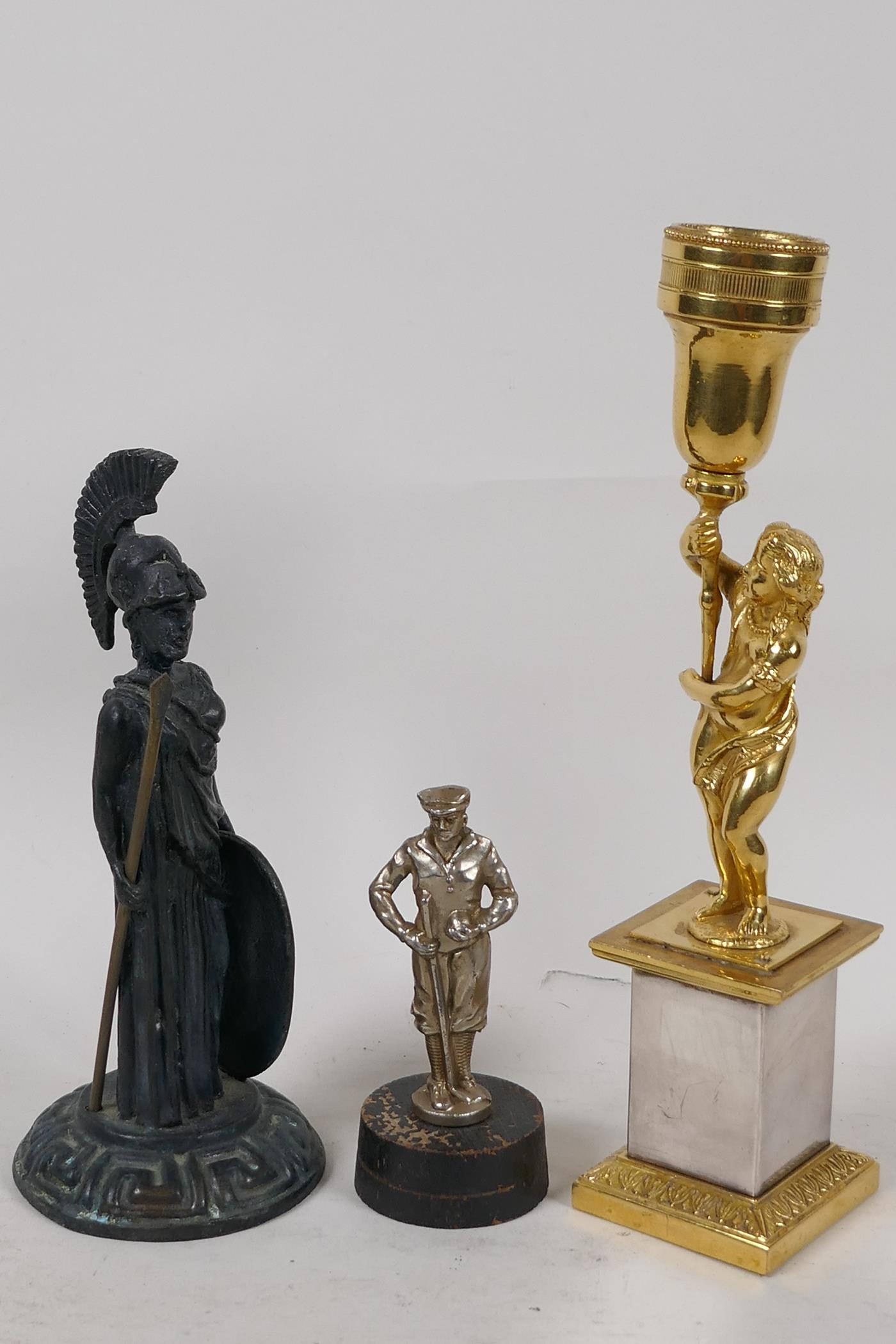"""A small bronze figure of a Roman soldier after the classic, 6"""" high, a brass figural candlestick and"""