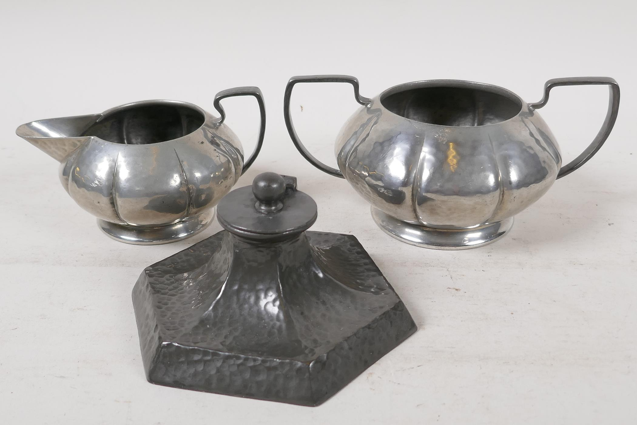 """An Arts & Crafts pewter inkwell by Talbot Pewter Co, 4½"""" wide, together with a Tudric pewter sugar"""