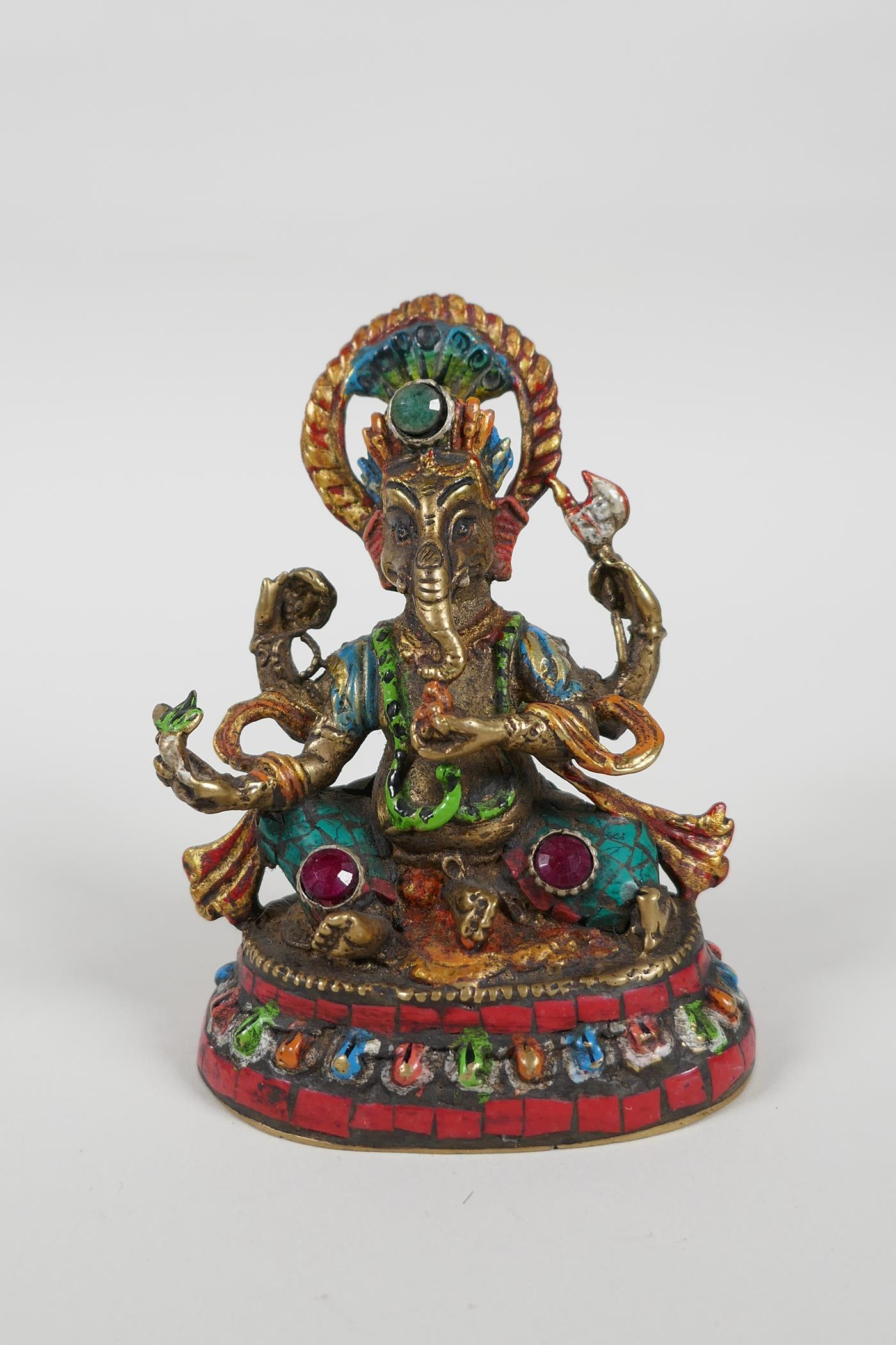 An Indian brass figure of Ganesh with painted highlights and set with semi precious stones, mark