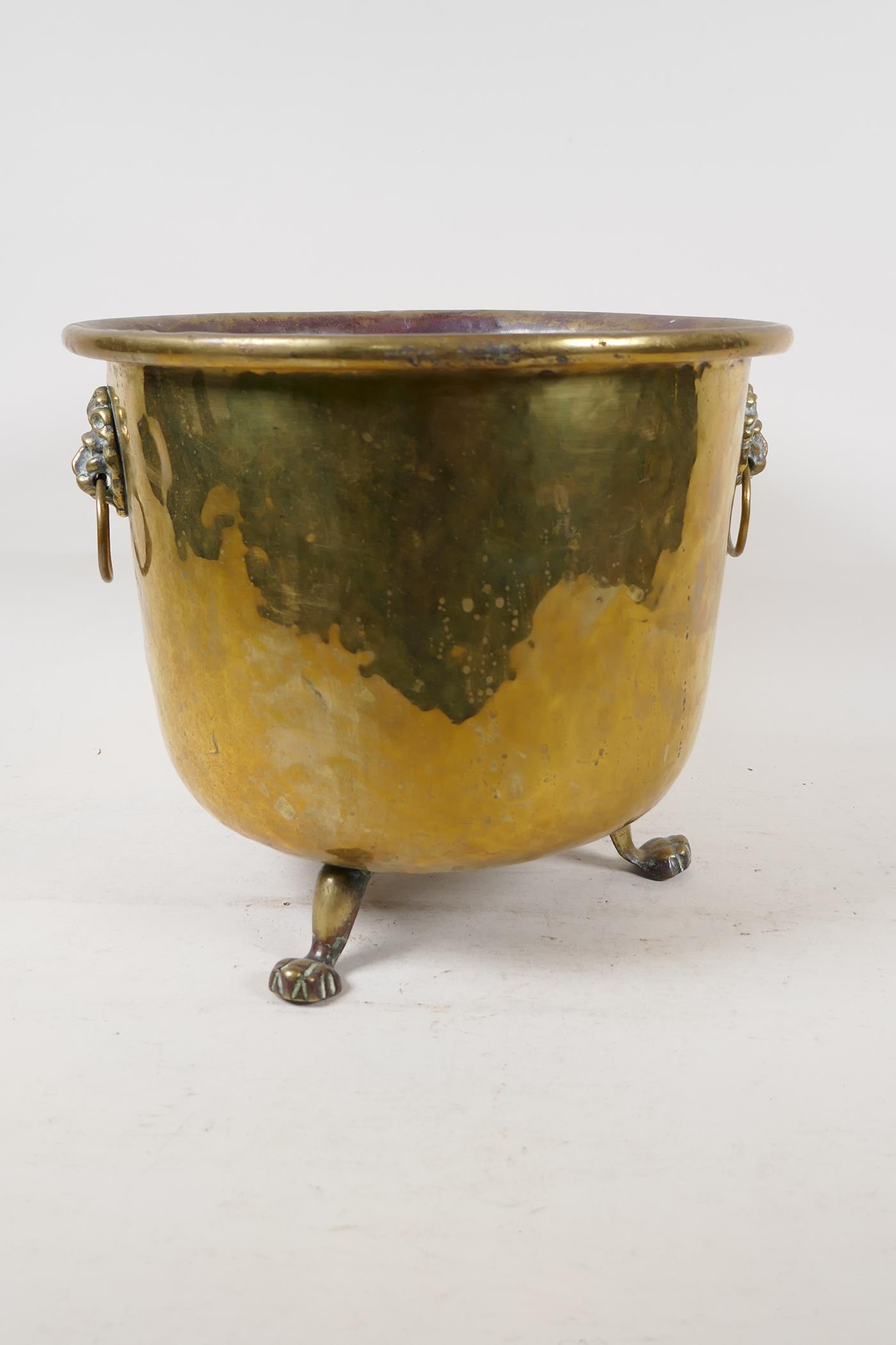 """A C19th polished brass jardiniere with lion mask handles and three paw feet, 9"""" high"""