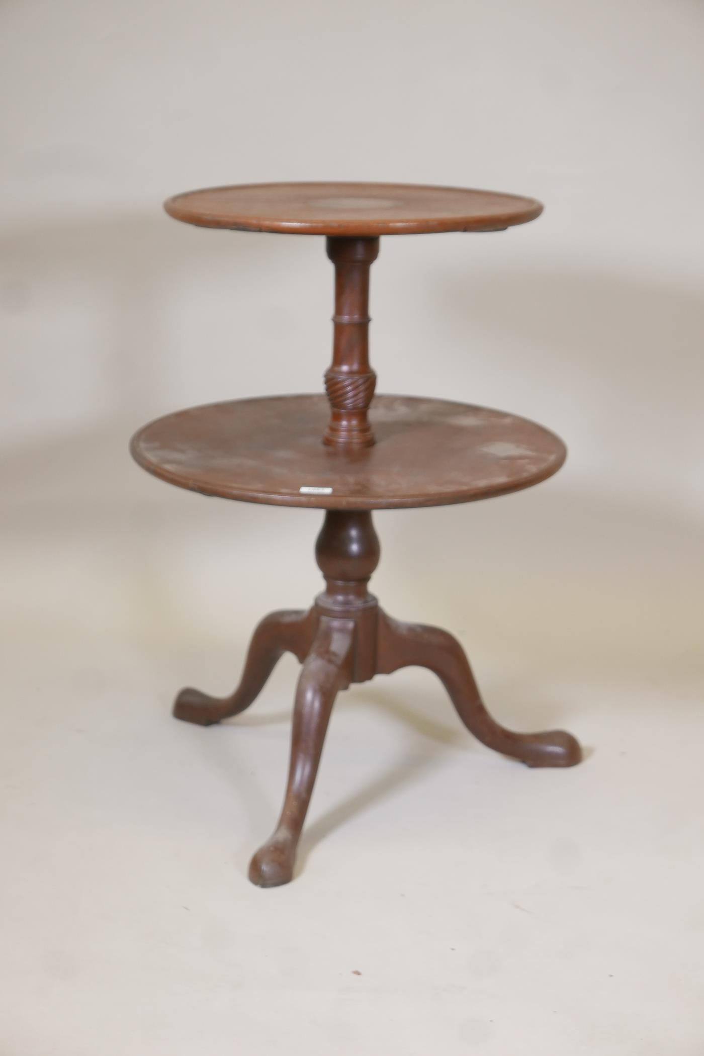 A George III mahogany two tier dumb waiter on a turned and carved column and tripod supports, A/F