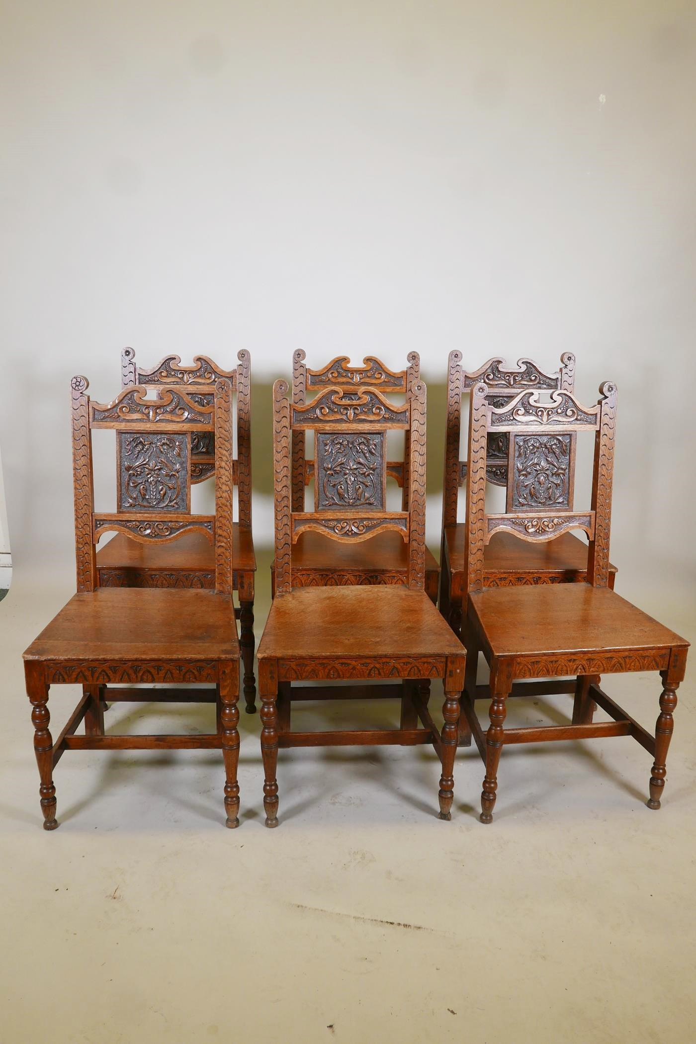 A set of six oak dining chairs with carved backs