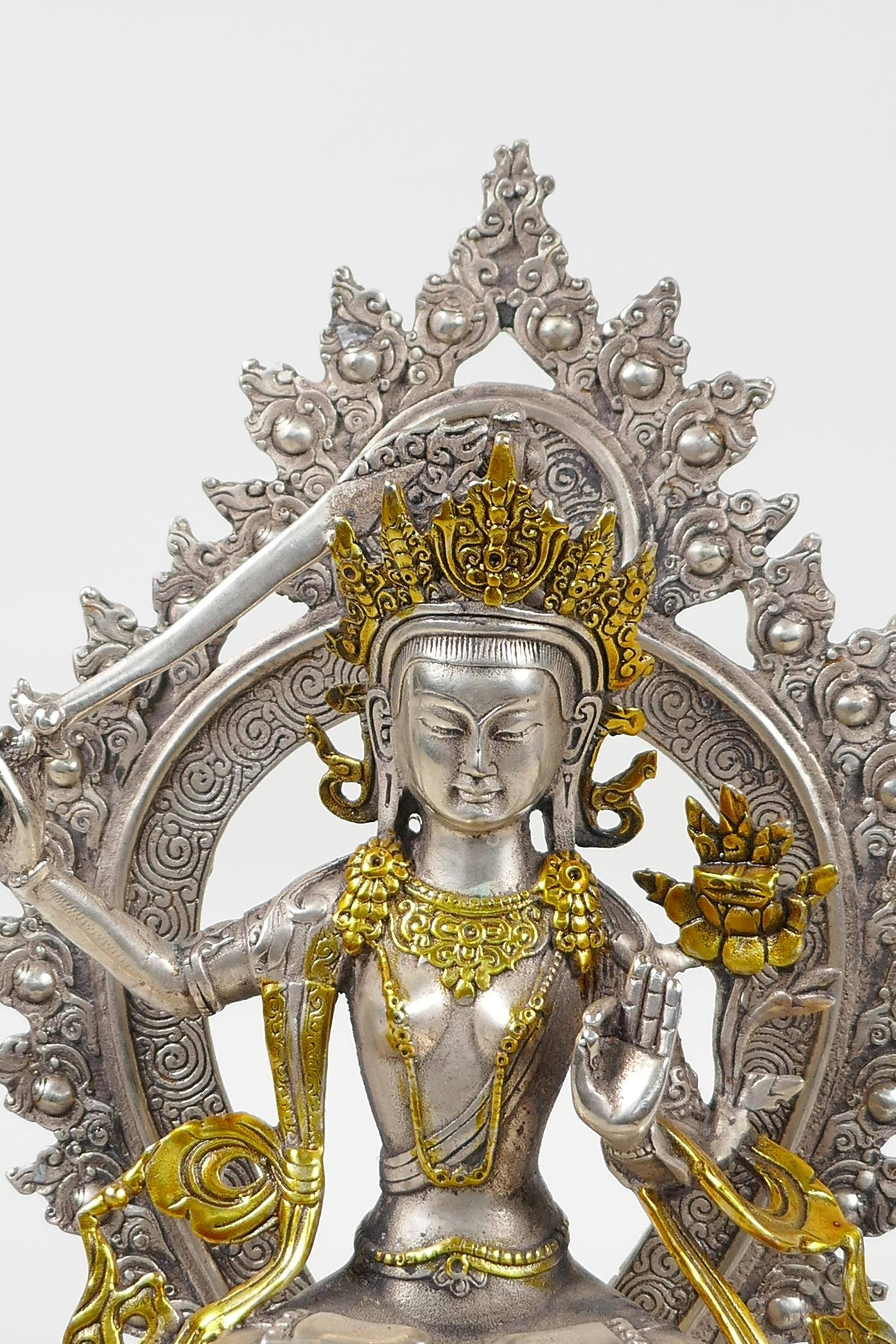A Sino Tibetan white metal figure of a seated deity carrying a sword with gilt highlights, double - Image 2 of 5