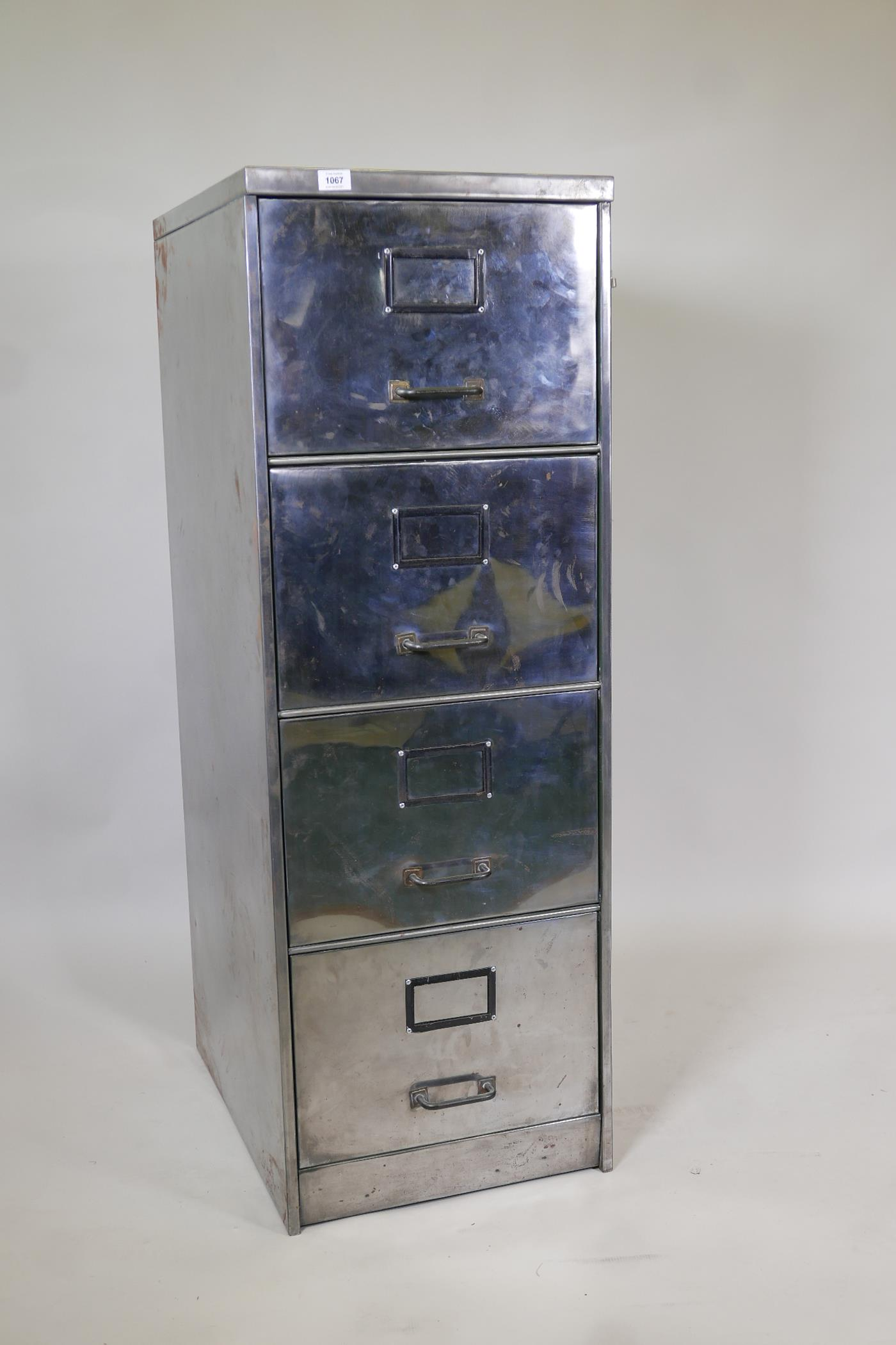 """A mid century stripped and polished metal four drawer filing cabinet, 1949 tag to the reverse, 18"""" x"""