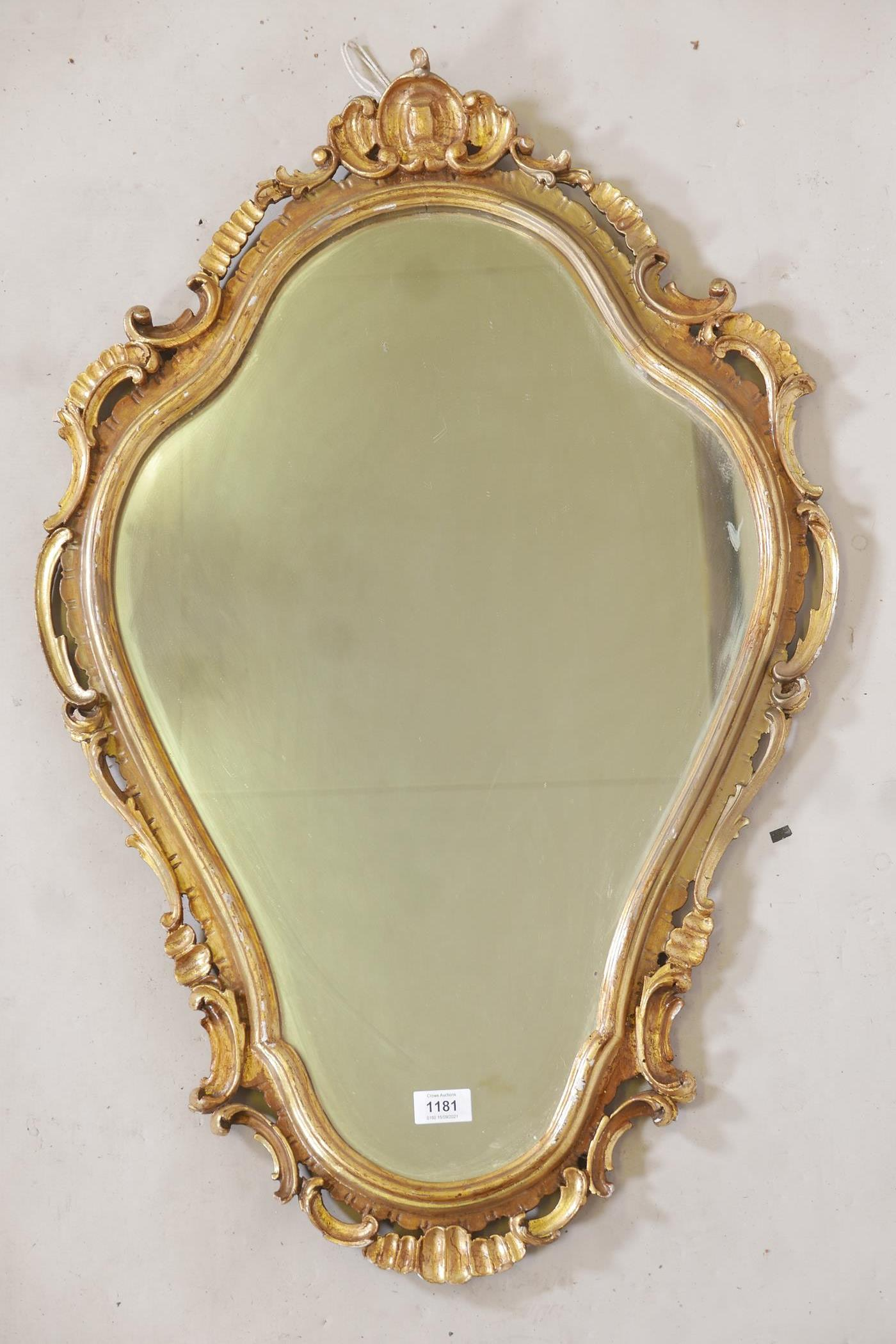 """A carved and pierced giltwood rococo style wall mirror, early C20th, 35"""" long"""