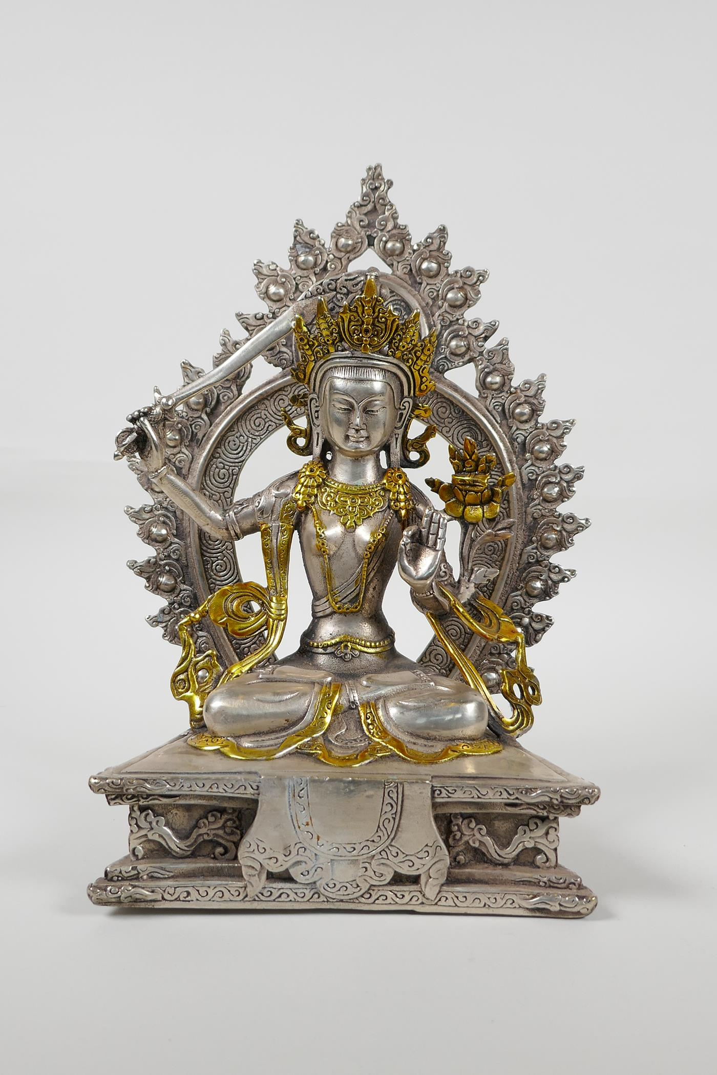 A Sino Tibetan white metal figure of a seated deity carrying a sword with gilt highlights, double