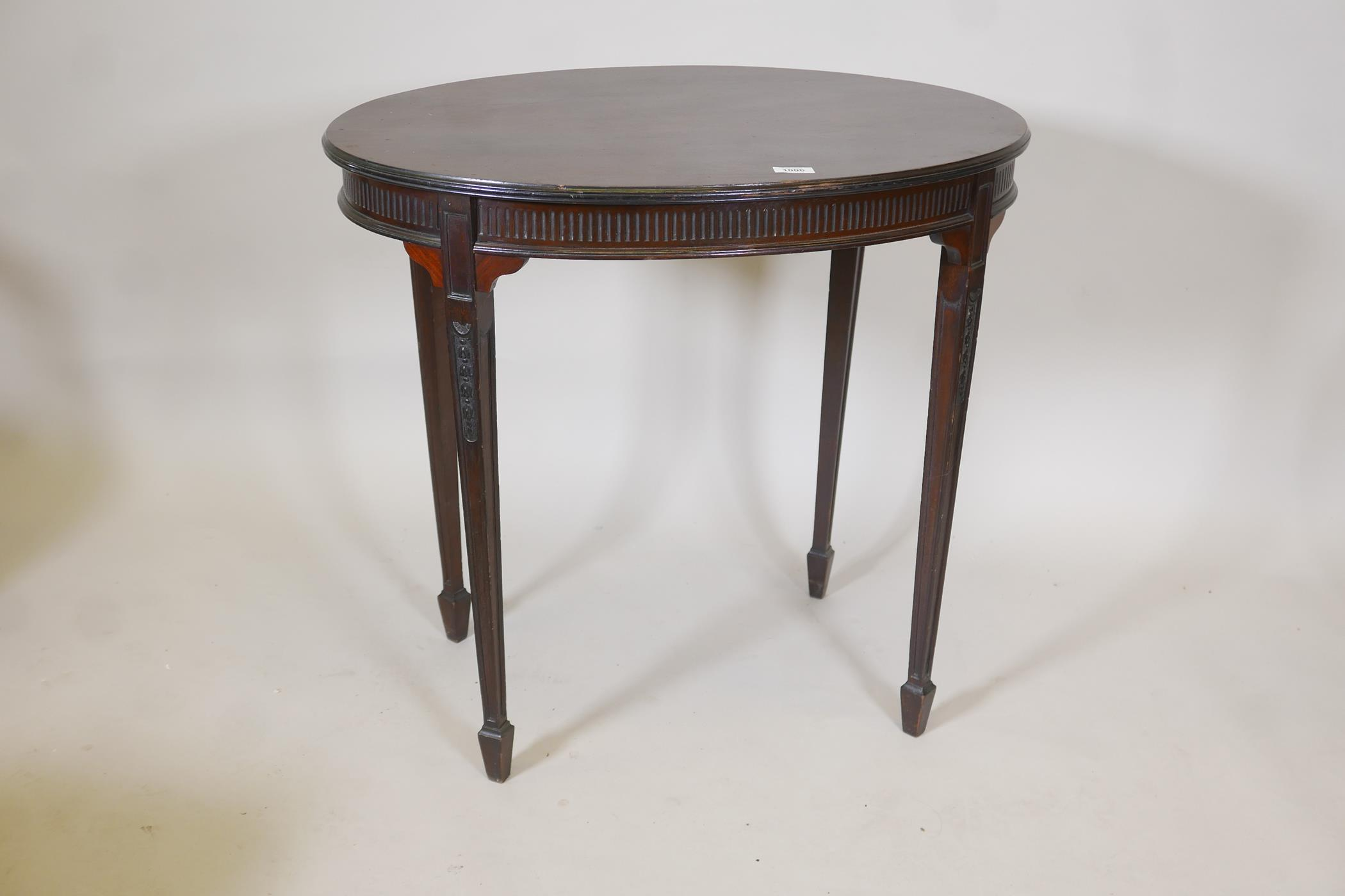 An Edwardian Adam style mahogany oval shaped occasional table, with reeded frieze and carved