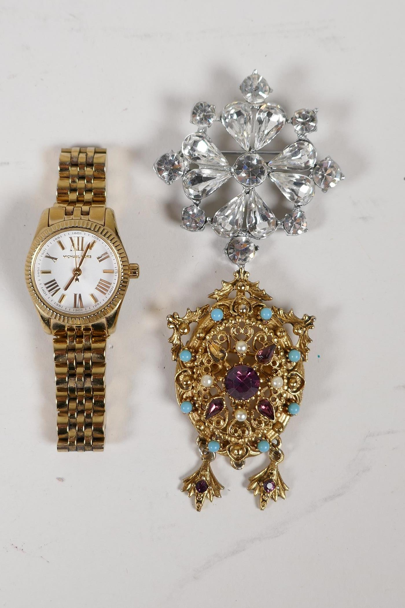 A lady's Michael Kors gold plated steel wrist watch, a vintage gilt metal brooch set with semi