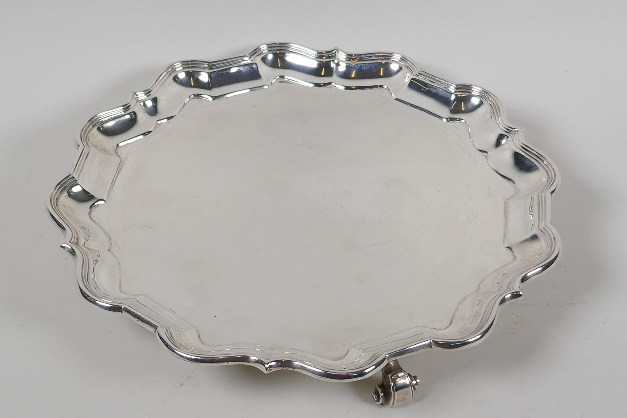 A hallmarked silver serving tray with gadrooned rim, on three cast scroll supports, hallmarked