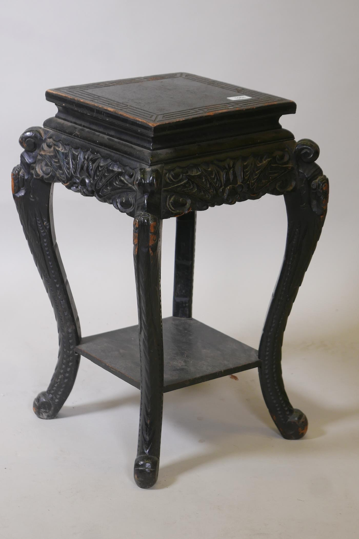 A Chinese two tier ebonised wood stand, with carved bat frieze, raised on scrolled shaped