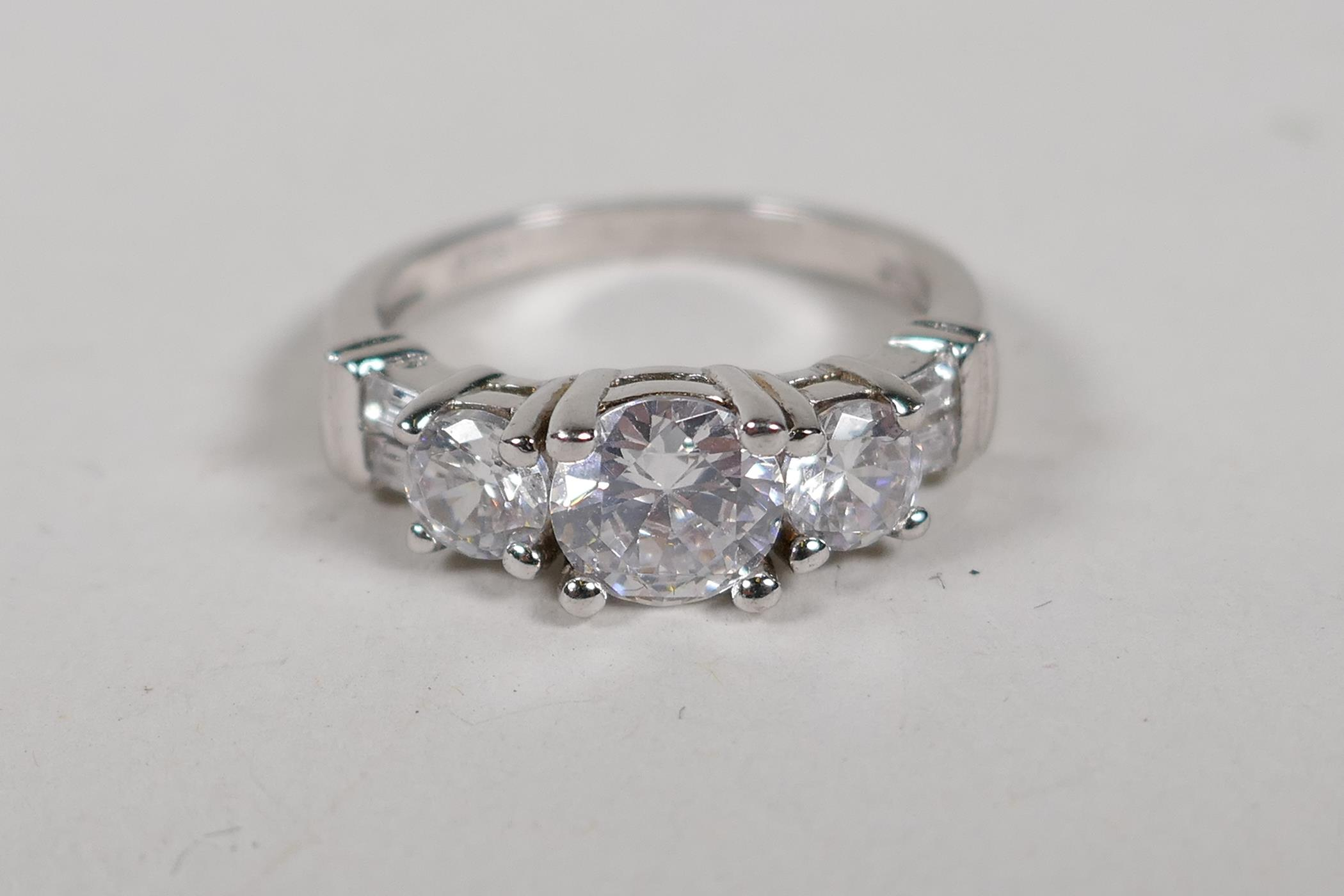 A 925 silver and cubic zirconia three stone dress ring, size N/O