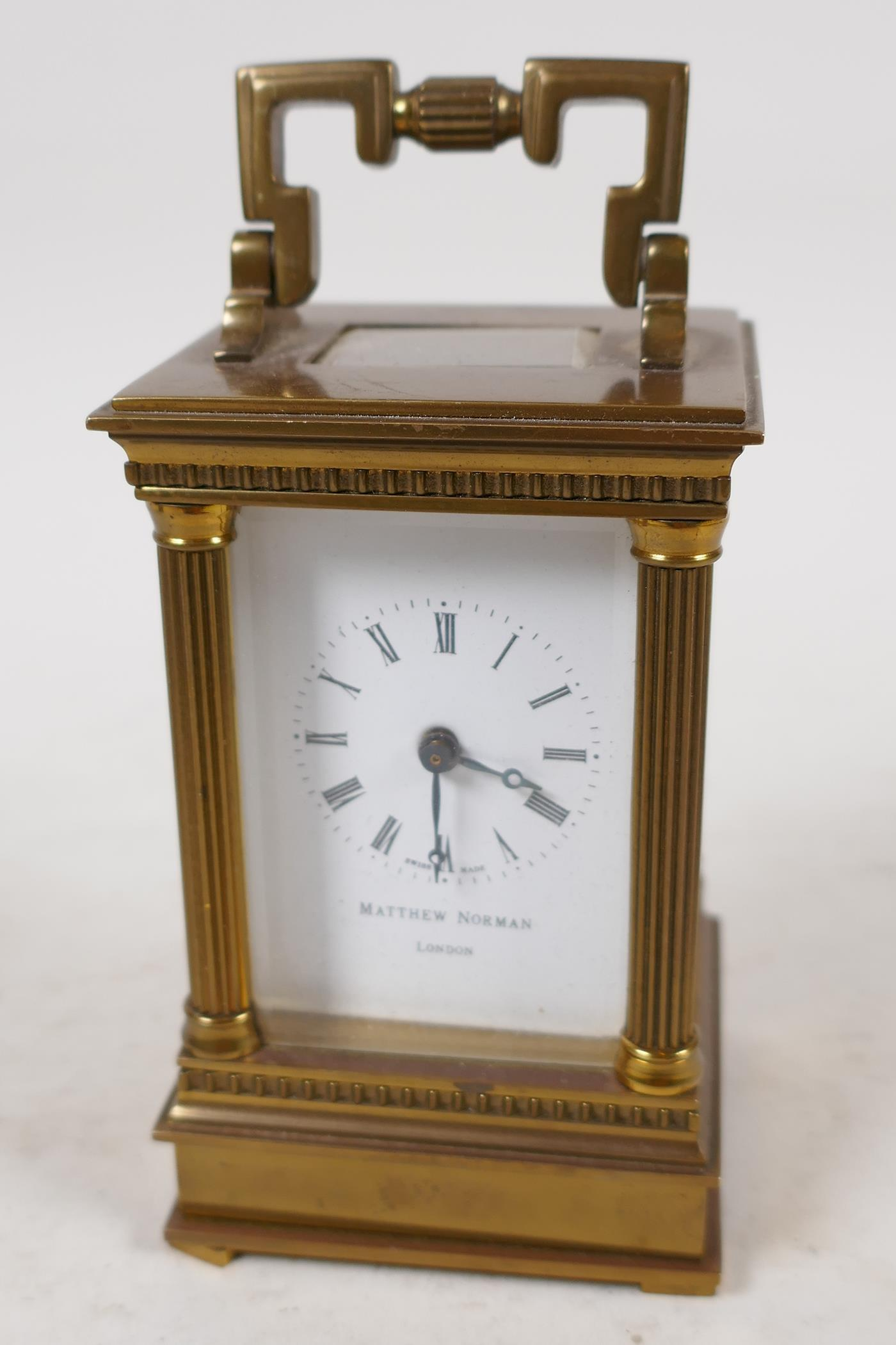 A Swiss made carriage clock in brass case with reeded columns, white enamel dial and Roman numerals,