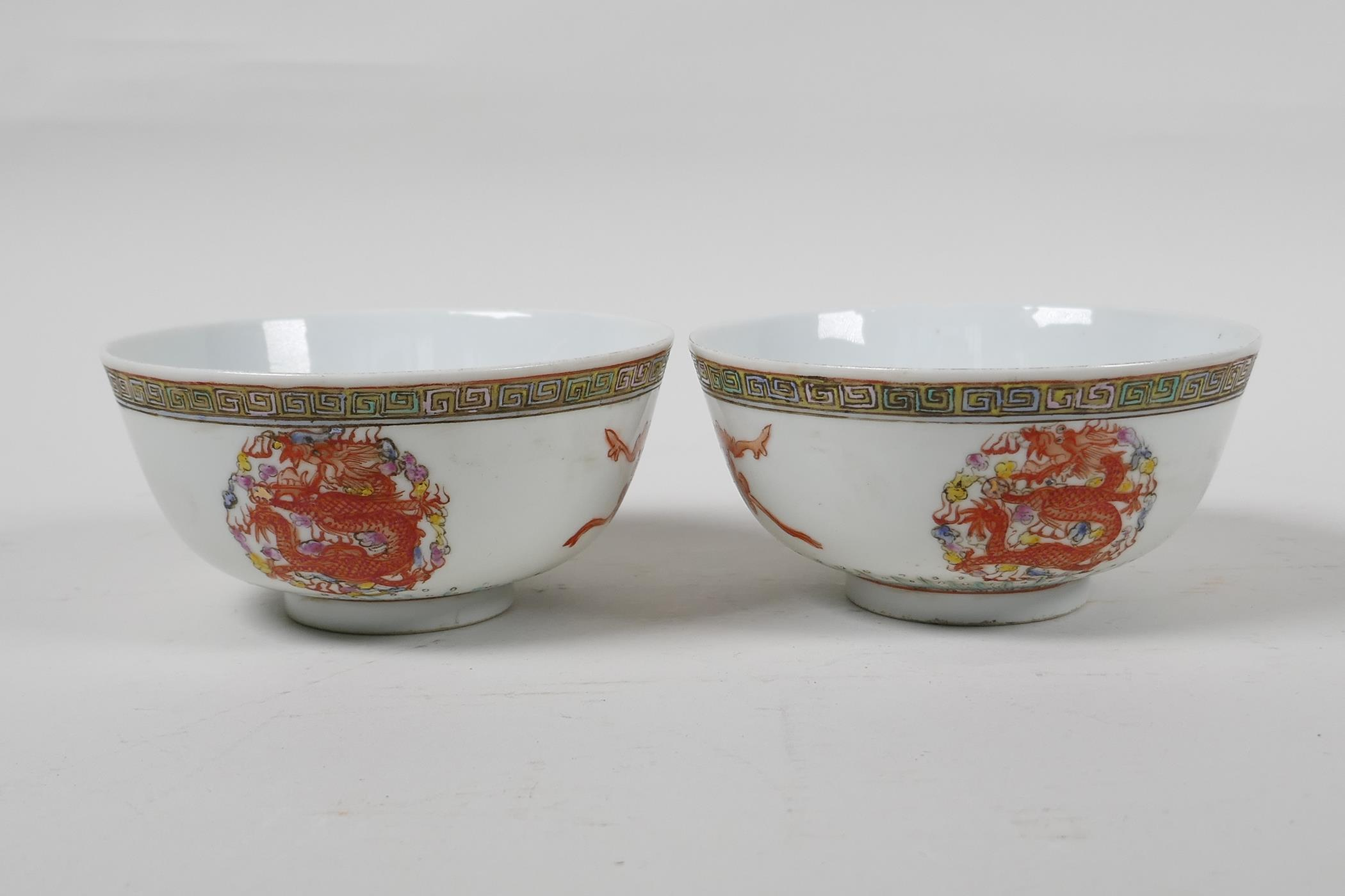 A pair of Chinese polychrome porcelain rice bowls decorated with auspicious items and dragons,