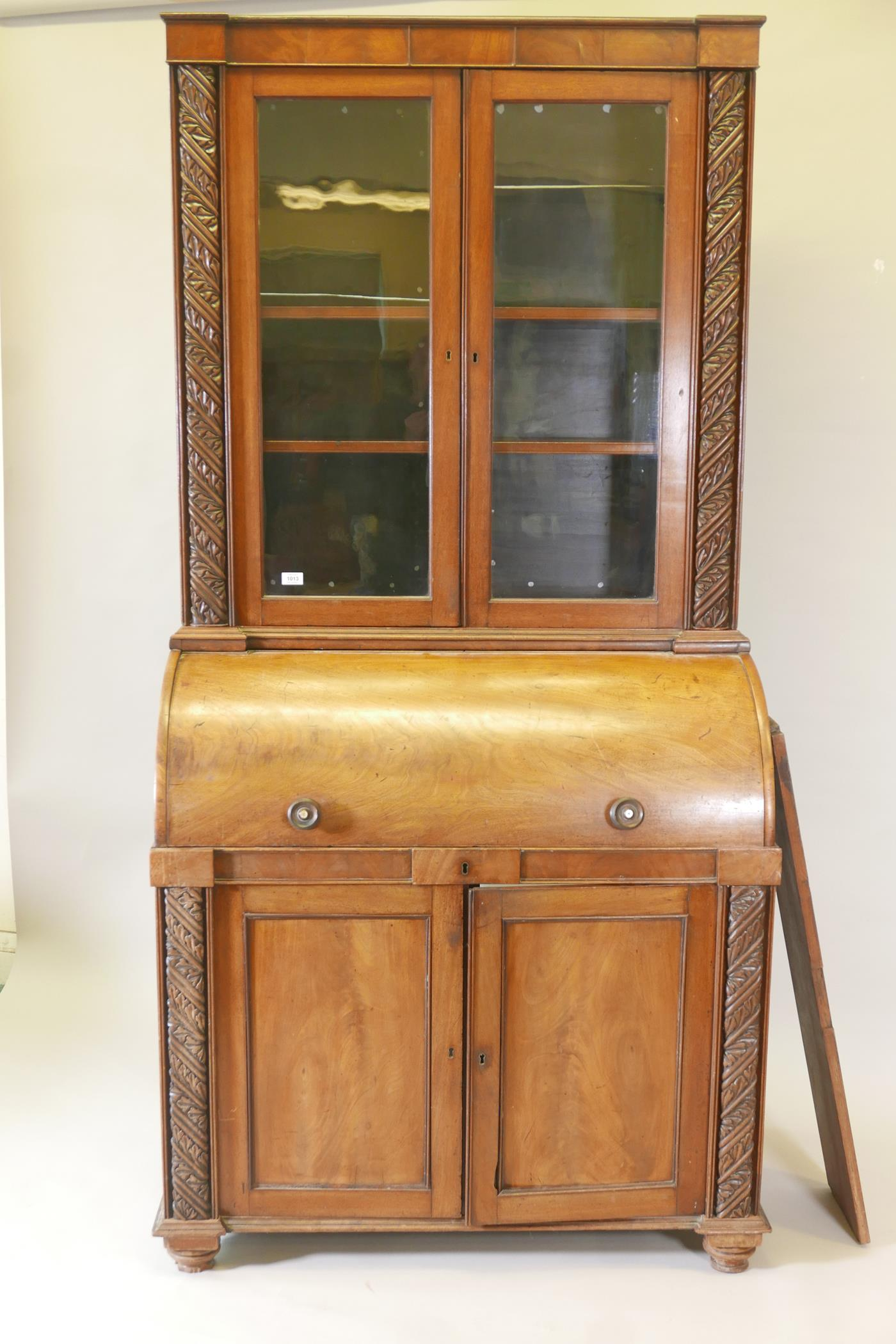 A Victorian cylinder top bureau bookcase, the upper section with two glazed doors and carved
