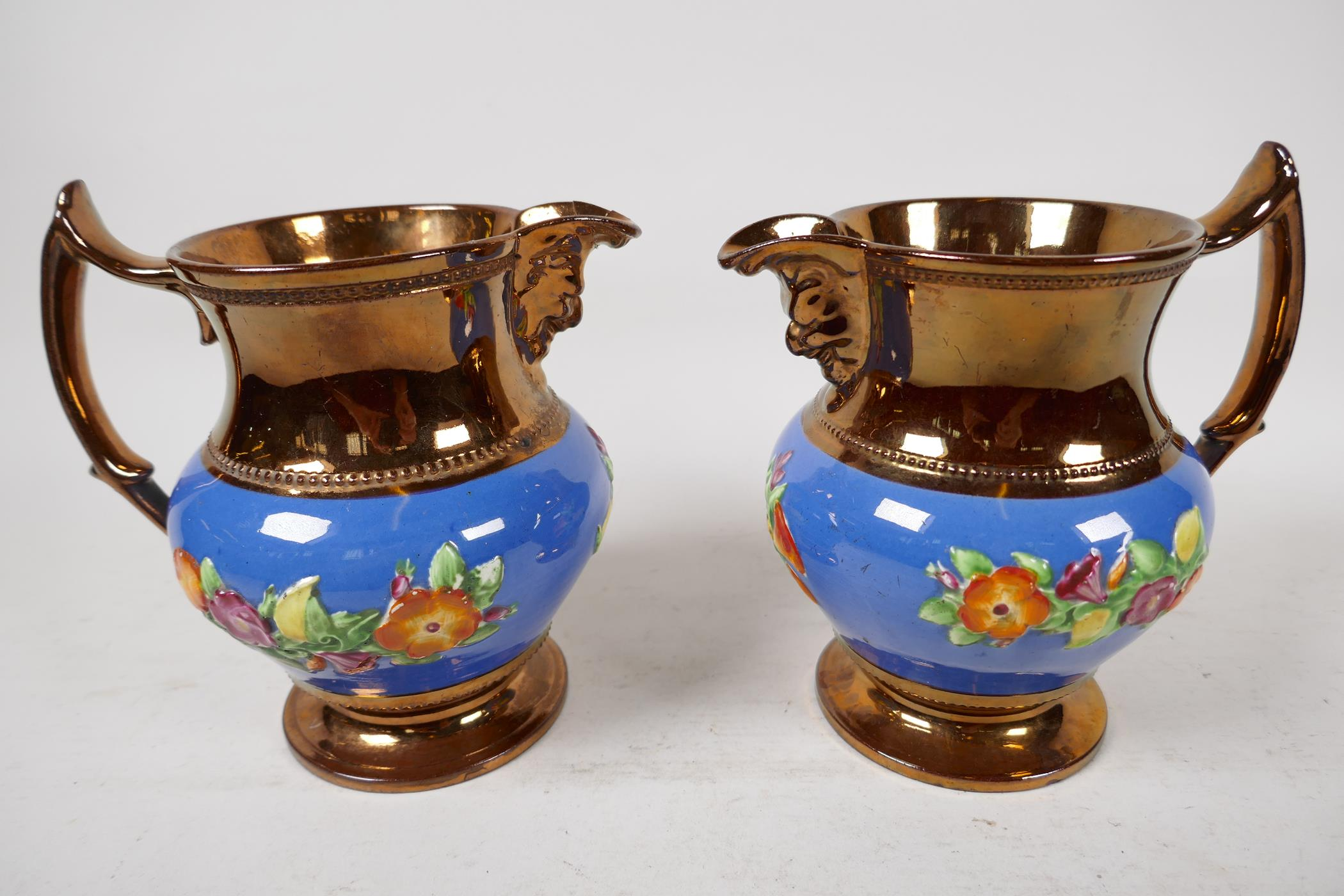 """A pair of C19th lustreware mask jugs decorated with embossed flowers, 6"""" high"""