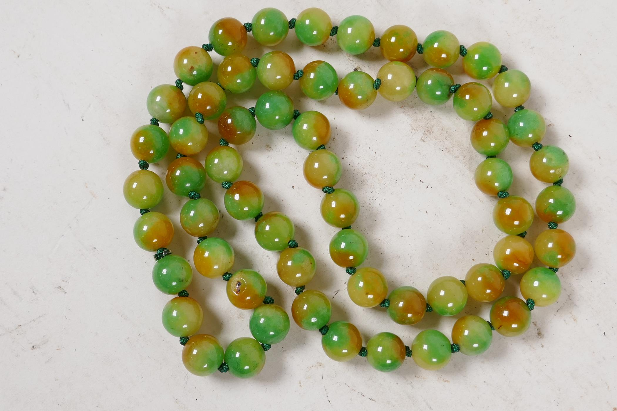 """A string of 60 two colour jade beads, 32"""" long"""