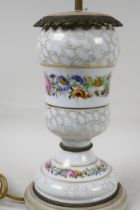 An urn shaped porcelain table lamp with ormolu mounts and painted with garlands of flowers, on a