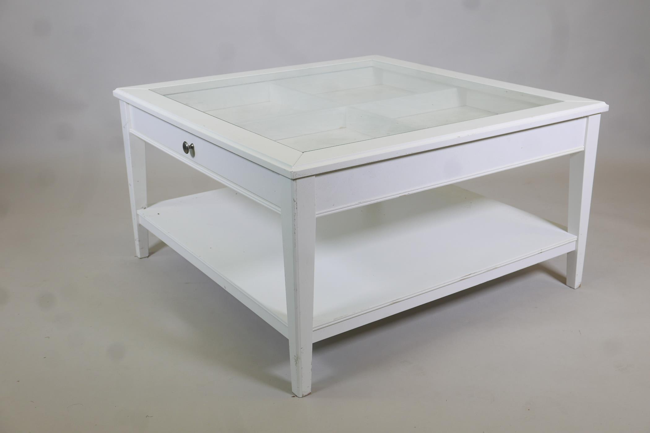 A painted coffee table with push-pull drawer and glass top, raised on tapering supports united by an
