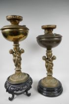 Two table lamps, the central bronze columns cast as two cherubs supporting an urn, with brass oil
