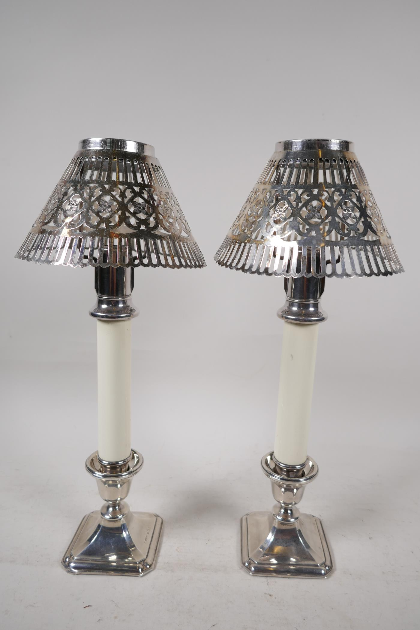 """A pair of table candlesticks with pierced silver plated shades on hallmarked silver bases, 12½"""" high"""