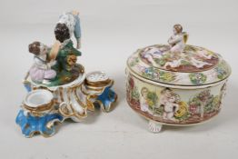 """A C19th continental porcelain inkwell modelled as two children on a seesaw, 6"""" high, and a"""