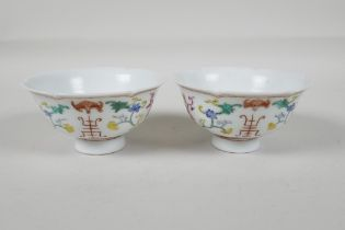A pair of early C20th Chinese polychrome porcelain tea bowls, with lobed rims and enamel