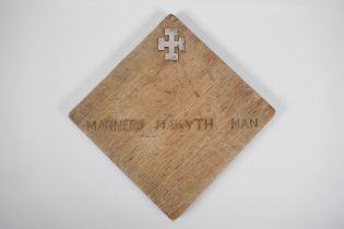 """An oak panel with inset hallmarked silver cross potent and the inscription, """"Manners Makyth Man""""."""