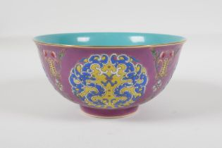 A Chinese polychrome porcelain rice bowl, decorated with stylised dragons, auspicious symbols &
