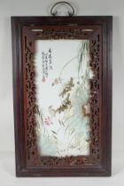 A Chinese famille vert porcelain panel, depicting birds perched on lotus flower stems, mounted in