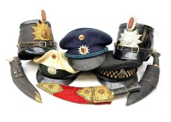 Four various 20th century German police hats; peaked cap with Metropolitan Police badge; and three k