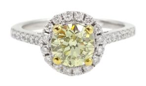 18ct white gold diamond halo ring, the central round brilliant cut fancy yellow diamond of 1.02 cara