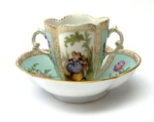 A Helena Wolfsohn Dresden porcelain quatrefoil twin handled chocolate cup and stand, painted with pa