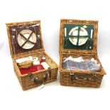 A wicker Amberley picnic basket, together with a wicker Optima example, each with contents. (2).