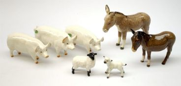 A group of Beswick figures, comprising two Charlie Wall Queen pigs, and a Charlie Wall Boy pig, two