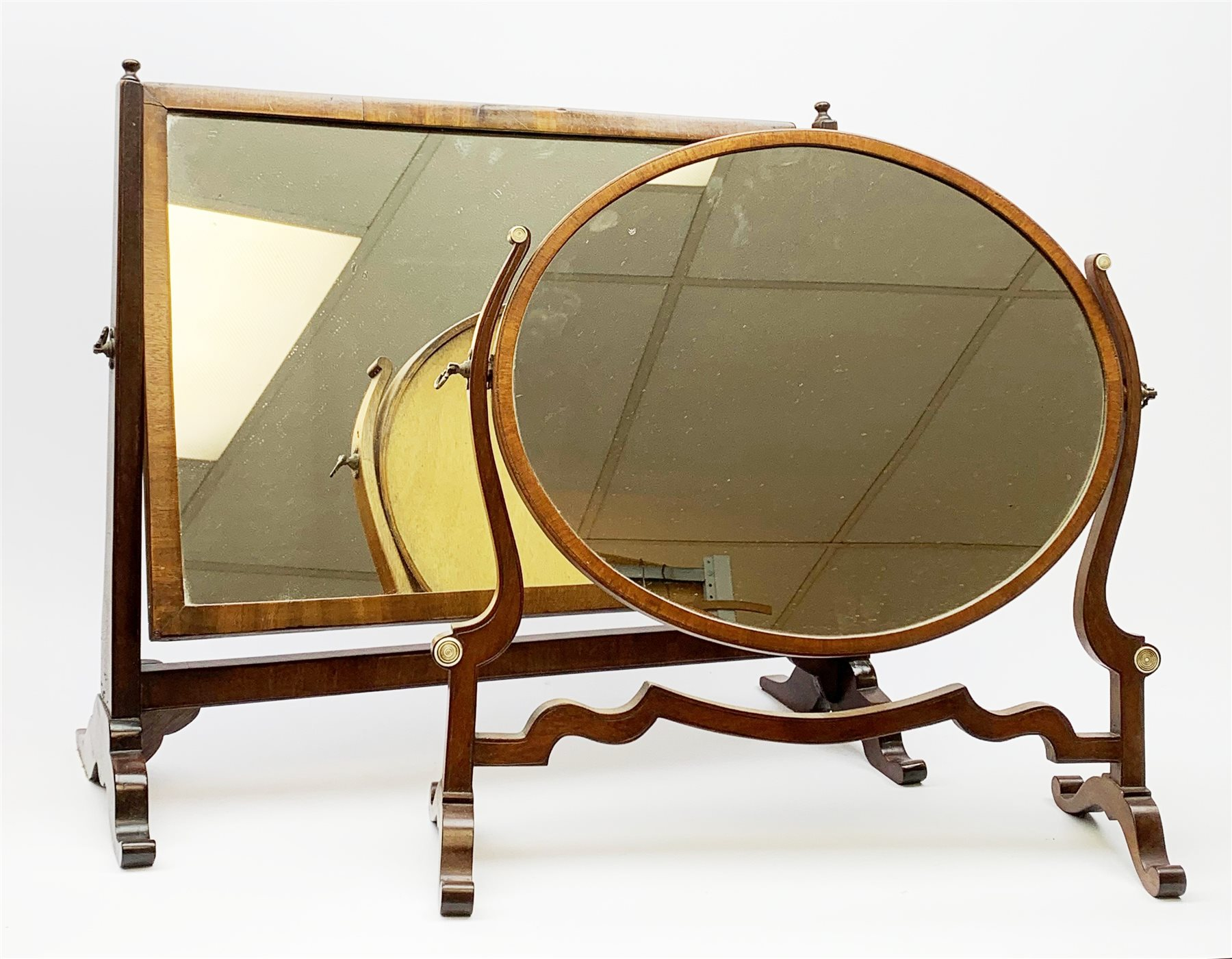 An Edwardian mahogany dressing table mirror, the oval mirror plate in swing frame, upon flared legs