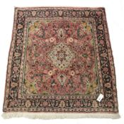 Persian pale red ground rug, the field decorated with flower heads, repeating guarded border, 117cm