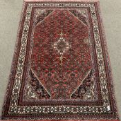 Large Persian red ground rug, central medallion, repeating border, 315cm x 210cm