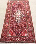 Hamadan red ground rug, repeating border, central medallion, 325cm x 170cm