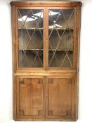 Large late 19th century sycamore corner cabinet, the top section with two astragal glazed doors encl