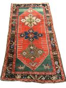Turkish red ground rug, the field decorated with three large stylised stars, two bird motifs to one