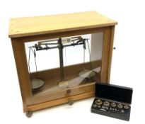 Set of Baird & Tatlock laboratory scales in oak case with rise-and-fall glazed front W39cm H36cm; wi