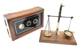 Set of brass and steel balance scales with rise-and-fall action on mahogany oblong base with moulded