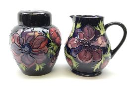 A Moorcroft jug decorated in the Anemone pattern upon a dark blue ground